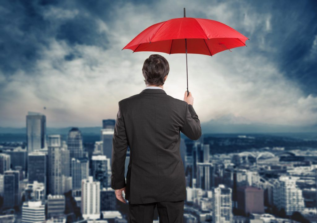 Man holding umbrella with view of city