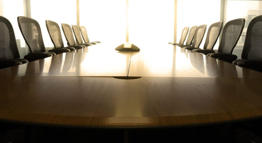 Conference table lined with chairs