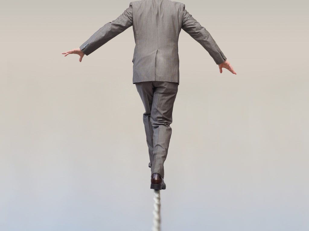Man in Suit Balancing on Pole