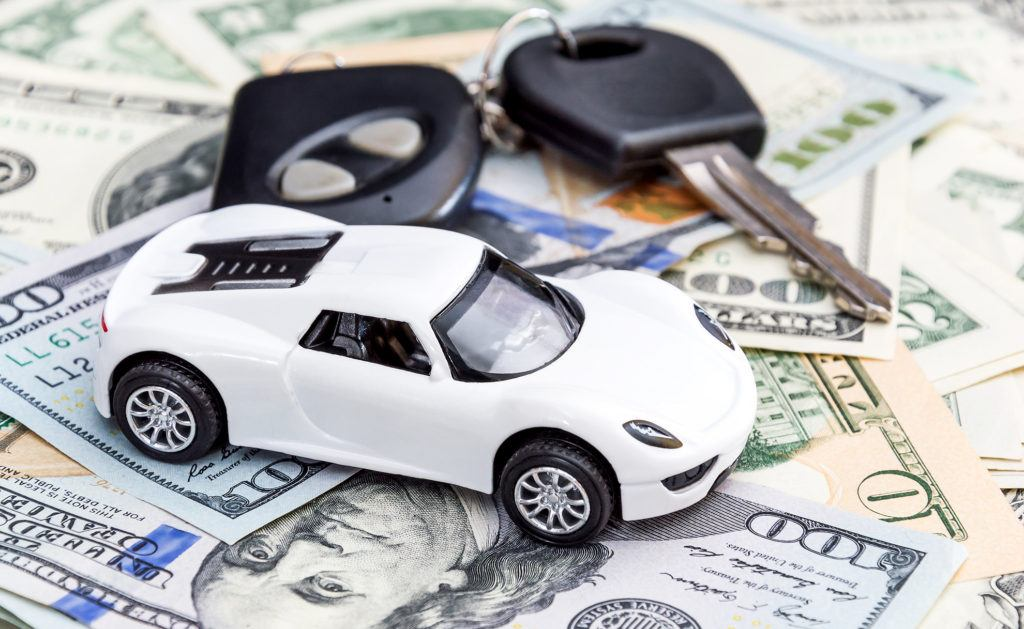 Toy car and keys sitting on pile of money