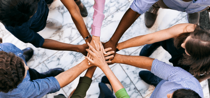 a diverse team of people standing in a circle with their hands in the middle