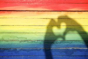 rainbow painted wall with shadow of hands making a heart